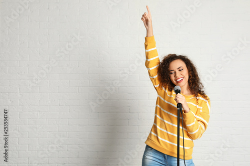Valokuvatapetti Portrait of curly African-American woman singing in microphone near brick wall