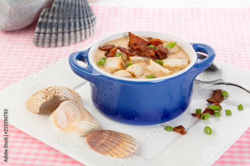Fotografie, Obraz  Blue Bowl filled with Seafood Chowder with Bacon Chips and Scallion Zest