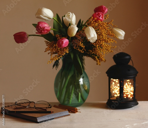 March 8,Easter,Mother's day concept /tulips in the vase,cup of coffee with marshmallows,open book ,glasses