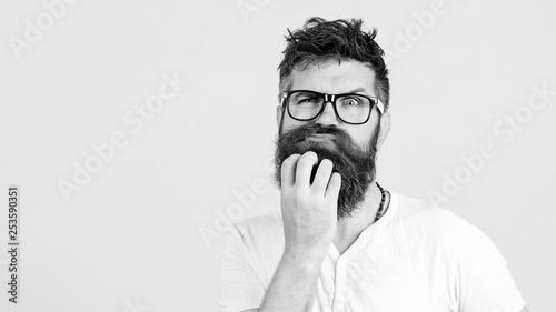 Pensive man touching his beard on white wall Canvas Print