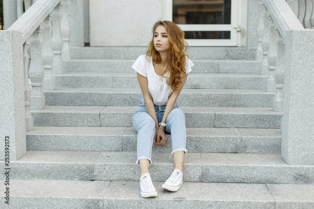 Fototapeta Attractive stylish young woman in a fashionable T-shirt in blue jeans in white trendy sneakers resting sitting on the steps of a vintage building. Cute european girl enjoying summer day.
