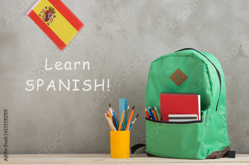 Foto  backpack, flag of the Spain and school supplies against a cement wall with text