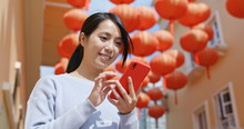 Woman Use Of Cellphone For Sending Red Packet With Mobile App Over Red Lantern Background