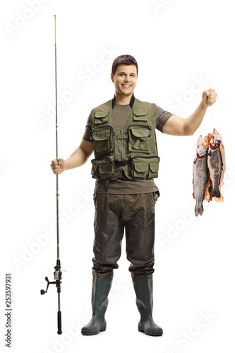 Obraz Young fisherman posing with a fishing rod and fish - fototapety do salonu