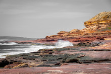 Waves Hitting Rock Coast With Different Colors From Red To Yellow In The Kalbarri National Park Australia Partly In Black And White