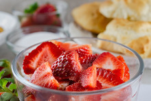 Close Up Veiw Of Sliced Strawberries In A Bowl Tossed Lightly With Sugar.  Additional Strawberries, Sugar, And Pastries In Background Blurred.