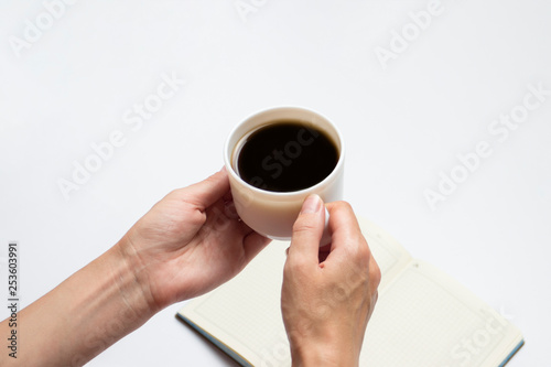 Fotografie, Obraz  Female hands hold a cup of black coffee and an open diary with clean pages, a pen on a light background