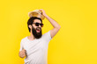 studio portrait of a cheerful bearded guy in a great mood, man in sunglasses, welcome gesture of raising the hat, concept summer vacation