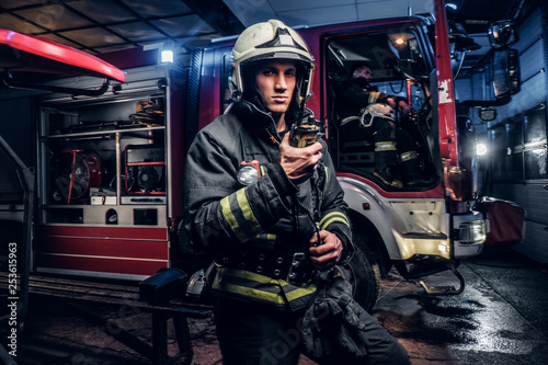 The fire brigade arrived at the night-time. Fireman in a protective uniform standing next to a fire truck and talking on the radio