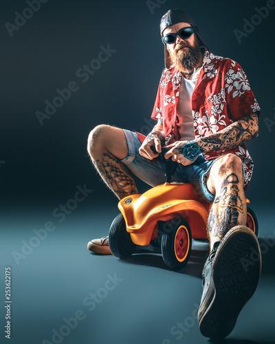 Cooler, tätowierter Mann mit Bart auf Spielzeugauto / Kurze Hose, Hemd und Sonnebrille Wall mural