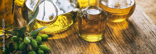 Obraz na plátně Olive oil in glass bottles on wooden table, banner, closeup view
