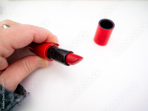 Fotografie, Obraz  hand holding red lipstick on white background