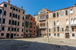 Italy, Venice, a group of people in front of a brick building