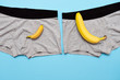 canvas print picture - baby banana compare size with big banana on male panties on blue background.