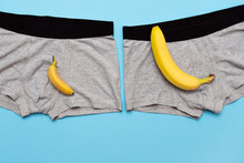 Baby Banana Compare Size With Big Banana On Male Panties On Blue Background.