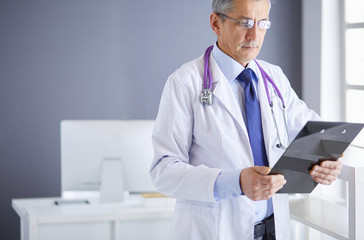Male doctor writes notes on the clipboard in the hospital
