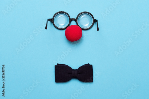 Funny glasses, red clown nose and tie lie on a colored background, like a face Fototapet