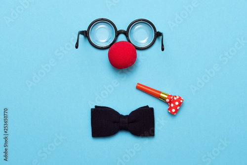Cuadros en Lienzo Funny glasses, red clown nose and tie lie on a colored background, like a face