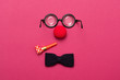canvas print picture - Funny glasses, red clown nose and tie lie on a colored background, like a face.
