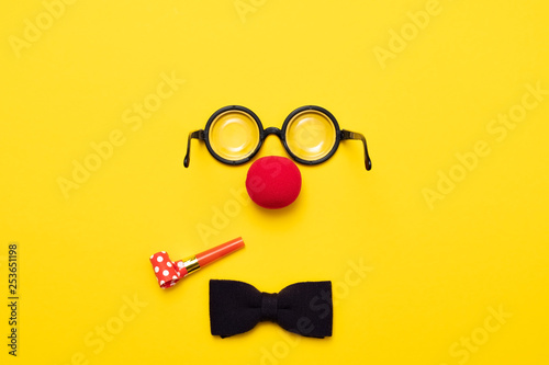 Fotografie, Tablou Funny glasses, red clown nose and tie lie on a colored background, like a face