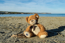 Teddy Bear Sitting Alone On The Sand On The Beach - Abandoned, Depresion, Violence Or Child Abuse Concept