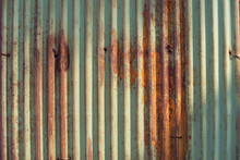 Old Green And Rusty Galvanized, Corrugated Iron Siding Vintage Texture Background Of Grunge. Image Taken With Beautiful Sun Light Cast On.