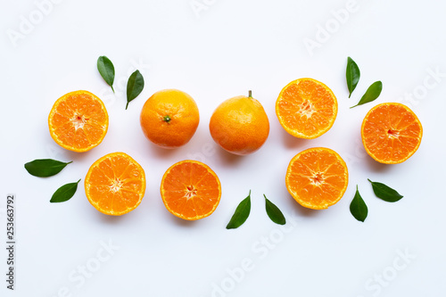 Orange fruits and green leaves on a white background.