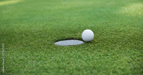 Obraz Golf ball and golf hole on green grass with copy space - fototapety do salonu