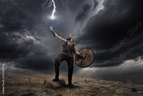 Photo  Medieval warrior berserk Viking with axe catch the lightning
