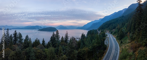 Aerial panoramic view of the scenic highway surounded by the Beautiful Canadian Mountain Landscape during a summer sunrise. Taken in Sunset Beach, North of Vancouver, British Columbia, Canada.