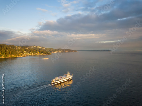 Foto Aerial view of a ferry boat in the ocean during a vibrant cloudy sunset