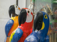 Close Up Of Three Large Carved Wooden Macaws In Rio