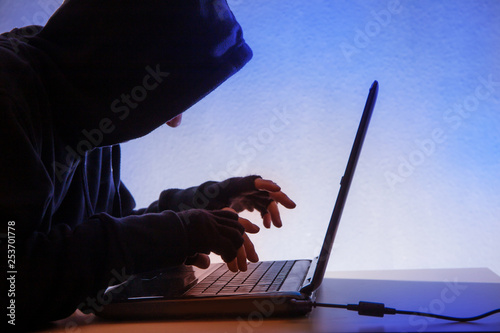 Fotografía  a hooded person sits in front of a computer