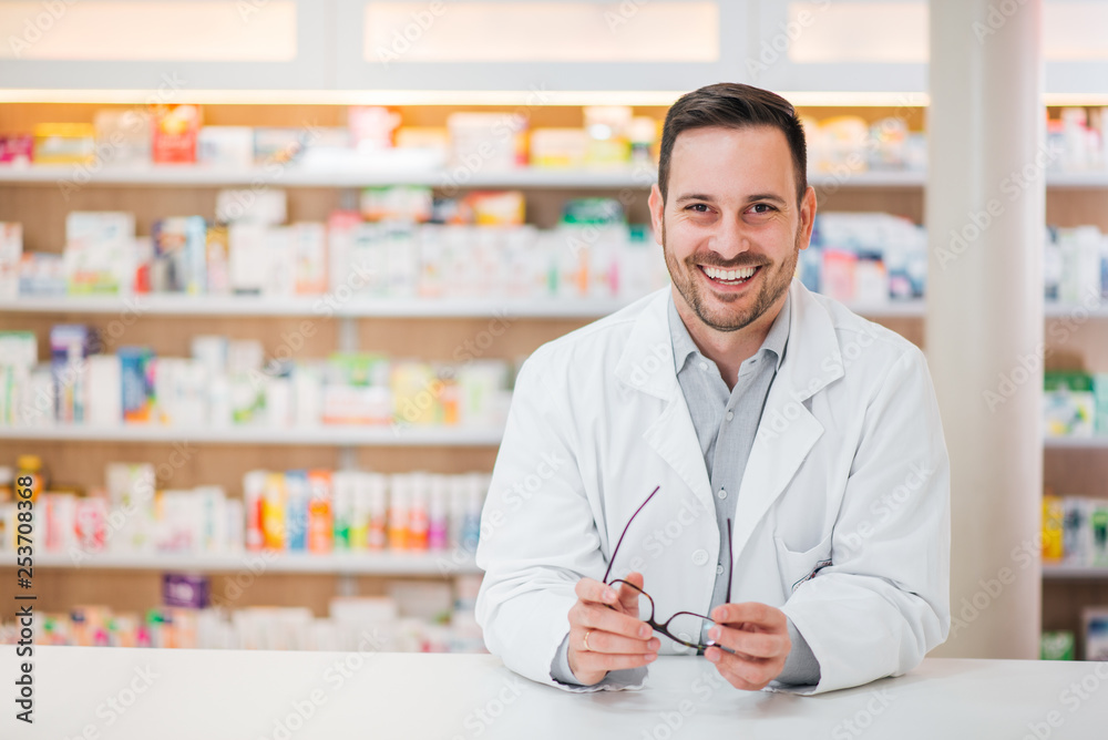 Fototapeta Portrait of a cheerful handsome pharmacist leaning on counter at drugstore.