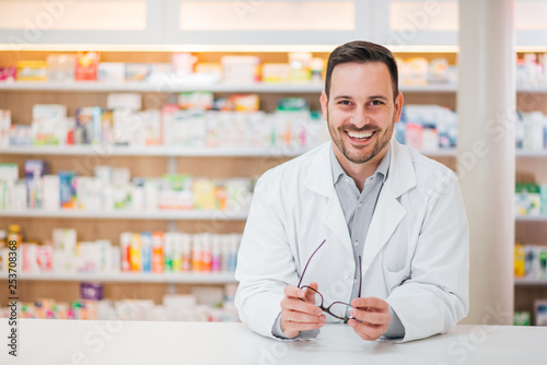 Spoed Foto op Canvas Apotheek Portrait of a cheerful handsome pharmacist leaning on counter at drugstore.