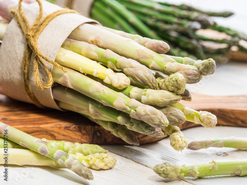 Bundles of green and white asparagus on wooden board Canvas Print