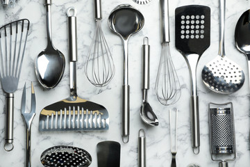 Different kitchen utensils on marble background, flat lay