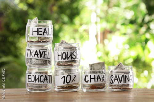 Fotografie, Obraz  Glass jars with money for different needs on table against blurred background