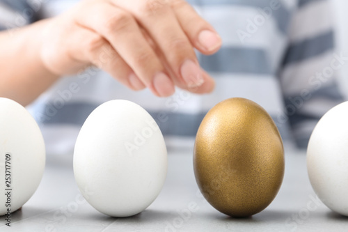 Obraz Woman choosing golden egg from white ones at table, closeup - fototapety do salonu