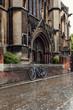 Mountain bike parked near church in Cambridge, rainy day