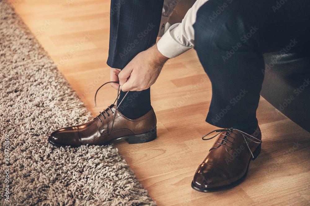 Fototapeta Mężczyzna wiąże buta