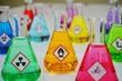 Leinwandbild Motiv Many of Erlenmeyer flask with colorful solution and Variety type of chemical hazard warning symbols labels. Focus on Oxidizing sign,symbol.
