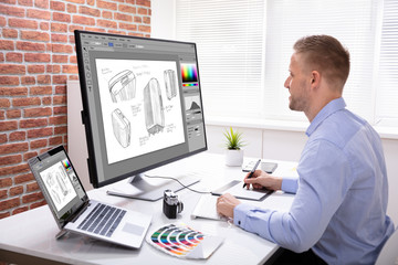 FototapetaDesigner Drawing Suitcase On Computer Using Graphic Tablet