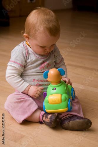 Fotografie, Obraz  Kleines Mädchen sitzt auf dem Fußboden und spielt mit Spielzeugauto