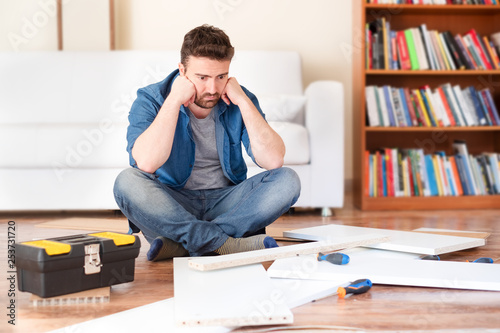 Photographie Sad young man reading the instructions to assemble furniture