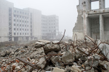 Fragments Of Concrete Stones With Protruding Reinforcement On The Background Of The Building In A Foggy Haze. Background
