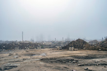 The Remains Of A Large Concrete Building In The Misty Haze In The Form Of Fragments Of Piles And Piles Of Stones.