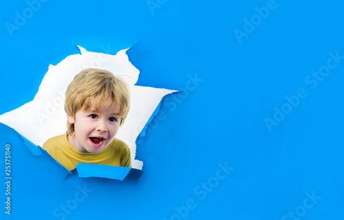 Cuadros en Lienzo  Smiling boy looking through hole in paper wall