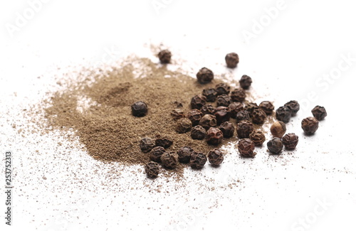 Black pepper grains and powder isolated on white background