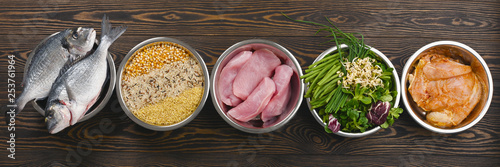 Panorama banner with healthy pet food ingredients with chopped raw turkey, fish, groats, greens and grains in individual bowls on brown wooden background. Flat lay.